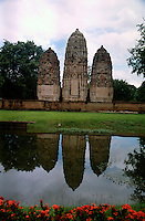 The Wat Phra Phai Luang. This somewhat isolated Wat features three Khmer - style prangs reflecting it's image in the lake. Sukhothai Historical Park, north central Thailand.