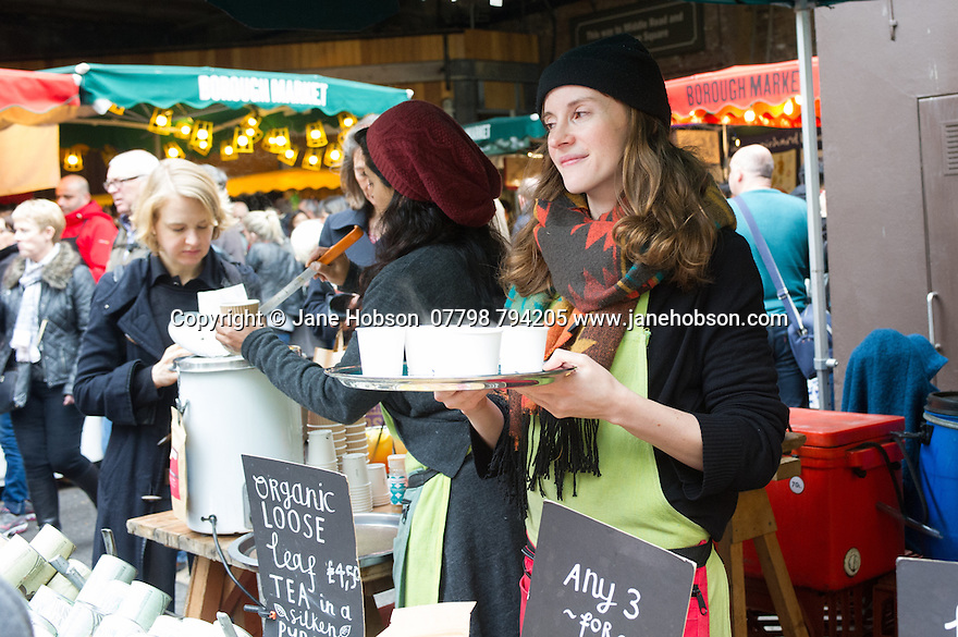 London, UK. 25.10.2014. a young woman serving herbal tea samples on Borough Market, Southwark. Photograph © Jane Hobson.