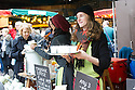 London, UK. 25.10.2014. a young woman serving herbal tea samples on Borough Market, Southwark. Photograph © Jane Hobson.