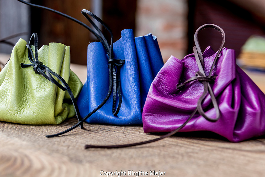 A green, a purple and a blue lhand made eather purse photographed up close. From an outdoor workshop in a small village in the Czech Republic