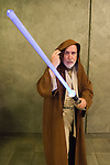 Garden City, New York, USA. November 30, 2013. Star Wars character Obi-Wan Kenobi, a Jedi Knight, wields his powerful lightsaber at the Winter holiday event Festival of Trees, held at Cradle of Aviation Museum during Thanksgiving weekend, with proceeds benefiting United Cerebral Palsy Association of Nassau County, Long Island.