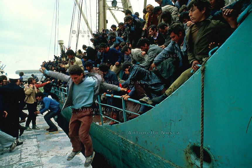 Brindisi, 8 Marzo, 1991. I passeggeri della prima grande nave carica di Albanesi si lanciano dalla nave appena attraccata nel porto di Brindisi.  Migliaia di Albanesi arrivarono al porto di Brindisi utilizzando ogni tipo di imbarcazione, dopo la caduta del regime comunista in Albania. A boat people arrive at the Brindisi harbor. It was March 8, 1991 when thousands of albanian refugees reached Italy after the fall of the comunist regime. The city of Brindisi, south Italy was invaded by a mass of desperate and poor people.
