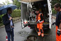 Baustadtrat Nils Kraft betrachtet mit den Kanalinspektoren Michael Dörrmann und Florian Hühn den Kamerawagen
