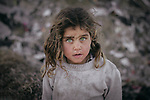 A poor girl with green eyes poses. Photo by Sanad Ltefa