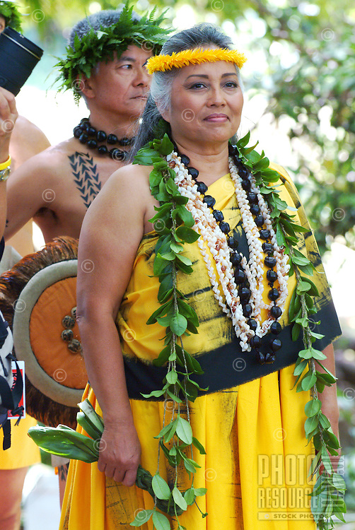 Kumu, or teacher, of hula followed by drummer at the Prince Lot Hula Festival in Moanalua Gardens on O'ahu. She wears lei made of maile leaves, black kukui nuts and shells.