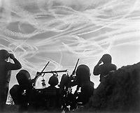 Alerted GIs of M-51 Anti-aircraft Battery are silhouetted against German sky streaked with vapor trails from allied and enemy planes engaged in Christmas Day dogfight.  Near Puffendorf, Germany.  December 25, 1944.  Pvt. M.S. Kelly. (Army)<br /> NARA FILE #:  111-SC-197661<br /> WAR & CONFLICT BOOK #:  1084