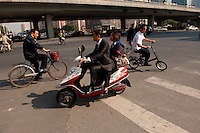 Daytime landscape view of a man wearing a suit driving a scooter at the intersection of Chao Yang Bei Lu and Dong San Huan Zhong Lu in Cháoyáng Q? in Beijing.  © LAN