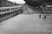 1977: boys beneath the Westway flyover throw stones at a London Underground train as it passes Acklam Road, Notting Hill.