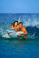 A happy family playing in the ocean on the Big Island coast