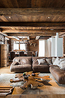 All of the furnishings in the living room evoke the woody, brown patina of an old log cabin, with a soft leather sofa, the heavy wooden table and the chandelier and wall lights made of antlers