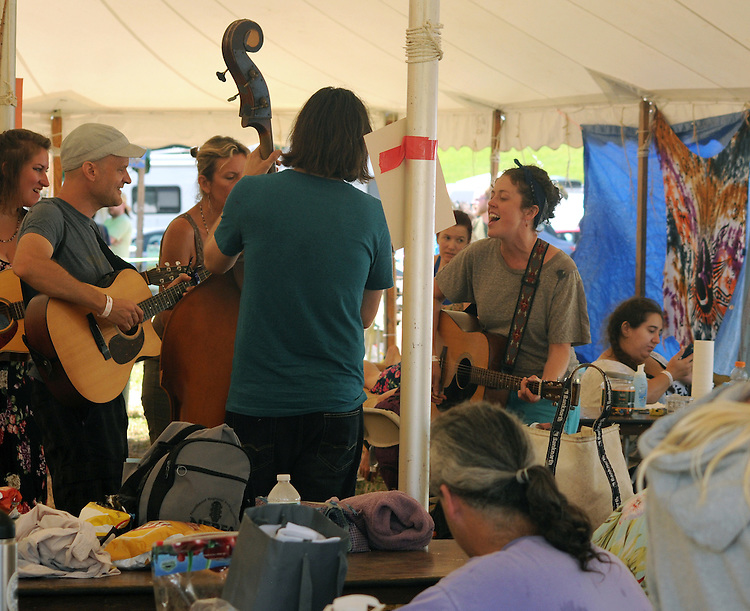 Volunteers play music in their headquarters tent at the Falcon Ridge Folk Festival, held on Dodd's Farm in Hillsdale, NY on Sunday, August 2, 2015. Photo by Jim Peppler. Copyright Jim Peppler 2015.