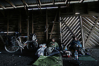 Gregg Bleakney and Don Thomas sip morning coffee in an abandoned barn while they wait for the wind to die down - Tierra del Fuego - Patagonia