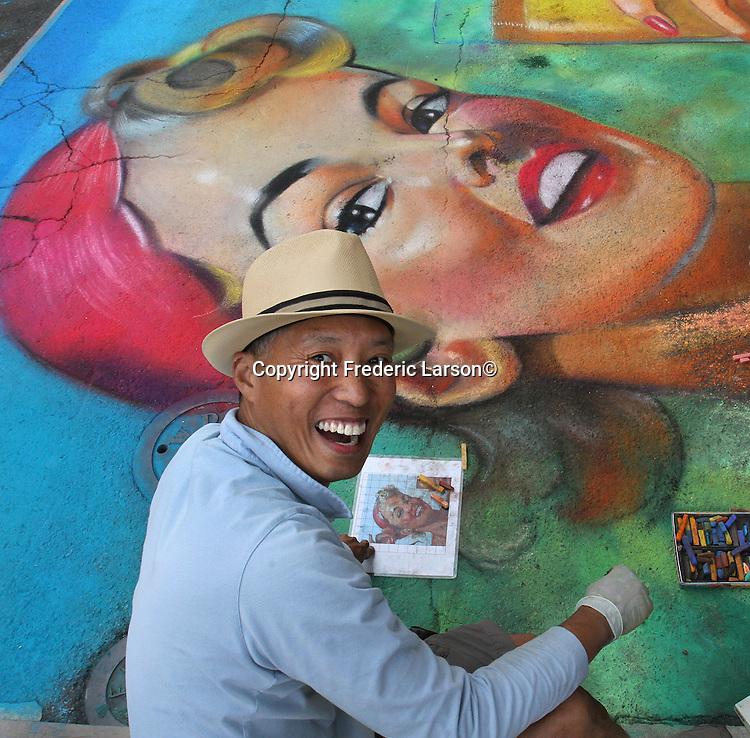 A street artist paints a portrait on Green Street during the Northbeach Art Fair in San Francisco, CA.