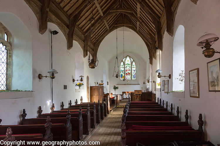 Looking east down the nave towards the altar and east window with historic wooden carved pews, fine wooden roof, whitewashed walls, interior of small village parish church at South Cove, Suffolk, England, UK