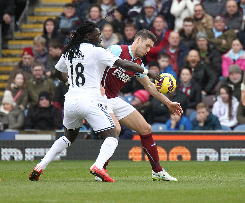 Burnley's Jason Shackell vies for possession with Swansea City's Bafetibis Gomis<br /> <br /> Photographer Rich Linley/CameraSport<br /> <br /> Football - Barclays Premiership - Burnley v Swansea City - Friday 27th February 2015 - Turf Moor - Burnley<br /> <br /> &copy; CameraSport - 43 Linden Ave. Countesthorpe. Leicester. England. LE8 5PG - Tel: +44 (0) 116 277 4147 - admin@camerasport.com - www.camerasport.com