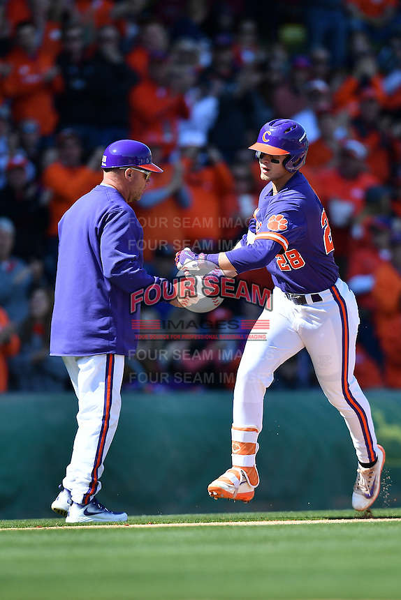 Left fielder Seth Beer (28) of the Clemson Tigers is congratulated after hitting a first-inning home run in the Reedy River Rivalry game against the South Carolina Gamecocks  on Saturday, March 4, 2017, at Fluor Field at the West End in Greenville, South Carolina. Clemson won, 8-7. (Tom Priddy/Four Seam Images)