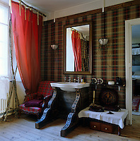 The tartan wallpaper of this bathroom is by Ralph Lauren and the silk taffeta curtains supported on knobbly branches are by Hermes