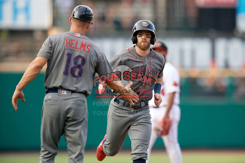 Lehigh Valley IronPigs center fielder Collin Cowgill (7) is congratulated by bench coach Wes Helms (18) as he rounds third base during a game against the Rochester Red Wings on June 30, 2018 at Frontier Field in Rochester, New York.  Lehigh Valley defeated Rochester 6-2.  (Mike Janes/Four Seam Images)