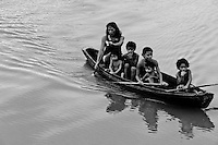 Indigenous kids with their mother paddle in the dugout canoe on the Amazon river, Brazil, 15 March 2004. Amazonia is the world's largest dense tropical forest area. Since the 16th century the original indigenous people have been virtually pushed away or exterminated. The primal ancient unity between tribes and the jungle ambient has changed into a fight between the urban based civilization and the jungle enviroment. Although new generations of white and mestizo settlers have not become adapted to the wild tropical climate and rough conditions, they keep moving deeper into the virgin forest. The technological expansion causes that Amazonia is changing rapidly.