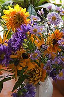 Detail of a vase of yellow and purple dahlias and daises