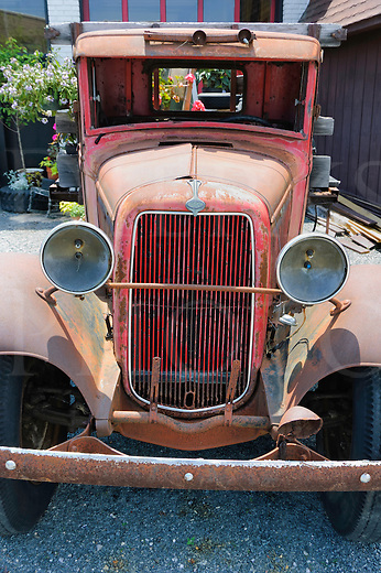 Old truck used as decoration with garden flowers, a 1930's Ford flatbed pickup, weathered, worn, and faded red.