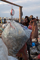 Girls weigh recyclables ona  scale in Dandora Dumpsite in Nairobi, Kenya. They will receive 3 shillings per kilo for materials that would sell at 9 shillings outside the dump.