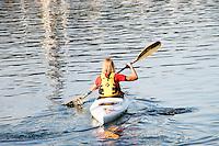 Blond woman rowing her white kayak - Denmark