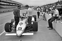 INDIANAPOLIS, IN - MAY 27: Bobby Rahal, driver of the 7-11 March 84C 06/Cosworth, speaks with crew chief Steve Horne (left) and engineer Adrian Newey (center) during practice for the Indianapolis 500 at the Indianapolis Motor Speedway in Indianapolis, Indiana, on May 27, 1984. Team owner Jim Trueman (right) sits on the pit wall.