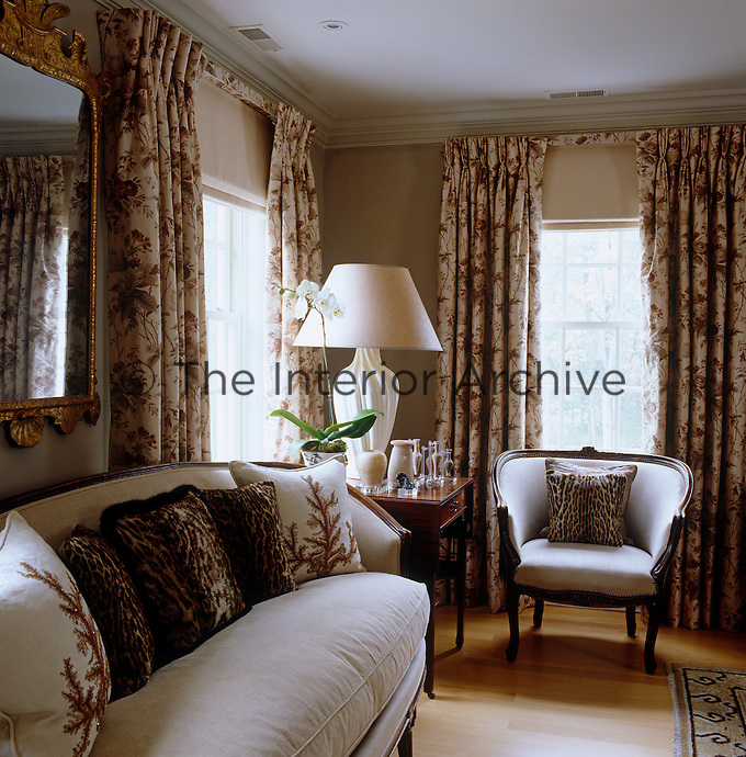 This seating area has been arranged next to a pair of large windows dressed with floral patterned curtains