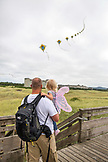 USA, Washington State, Long Beach Peninsula, International Kite Festival, father and daughter admire a line of thirty or more kites all on one string
