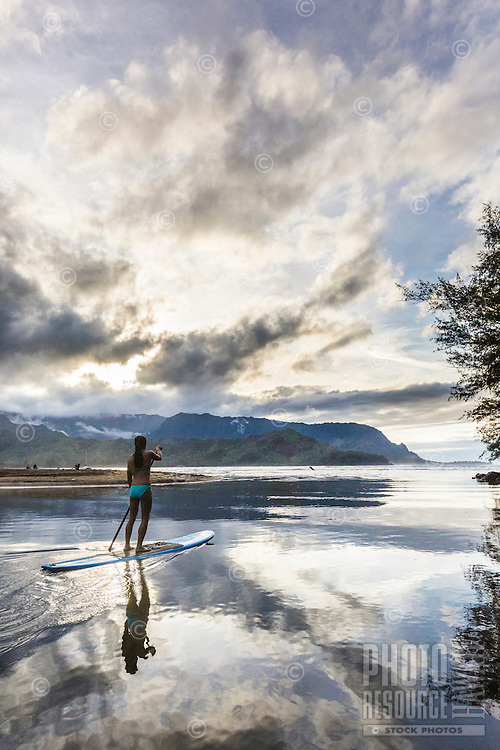 At sunset, a young woman paddles her board through the calm, reflective waters of Hanalei River, Kaua'i.