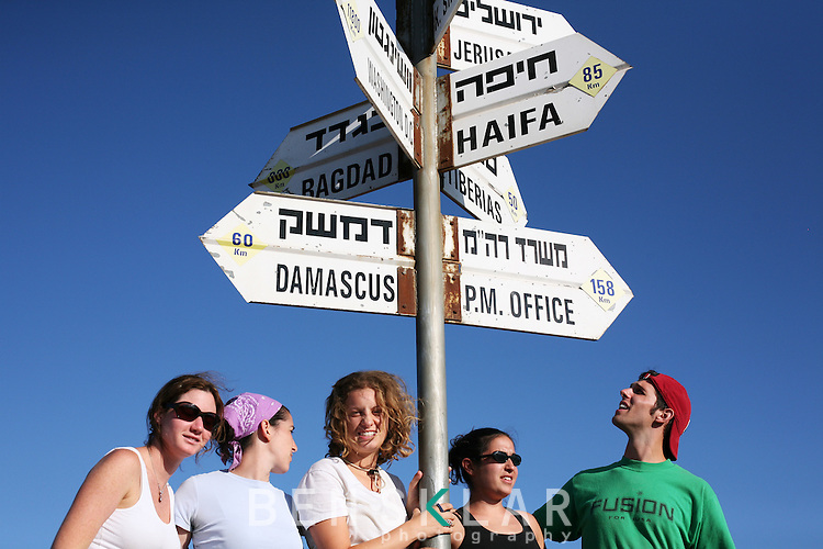 "Birthrighters pose for photos beneath a direction and distance sign post while touring the Golan Heights of Israel near the Syrian border. For the past seven years philanthropists have funded seasonal trips, known as ""Birthright,"" for children around the world of Jewish descent to explore Israel and learn about their heritage with their peers. An estimated 25,000 young people participate each summer."