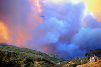 870000032 a large dual engine prop fire fighting aircraft emerges from a monstrous smoke cloud above an isolated home in the simi hills above chatsworth in north los angeles county during a massive 250,000 acre wildfire in california