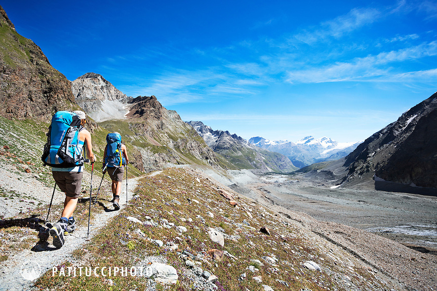 After leaving the Stockjigletscher on the fifth day of the Chamonix to Zermatt Glacier Haute Route, hikers descend a pleasant trail on dirt and rock above glacier debris with stunning views of the Dent d'Herens and Matterhorn.