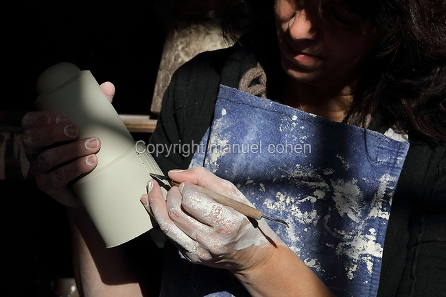 Ceramicist Valeria Polsinelli at work incising stripes into a clay pot, photographed in 2017, in her studio in Montreuil, a suburb of Paris, France. Polsinelli creates everyday vessels, water jugs, jewellery and figurines and stoppers of female busts, with features and hairstyles from various world cultures. Picture by Manuel Cohen