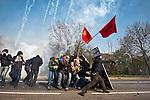 Abrite derriere un bouclier improvise, un manifestant lance une pierre sur les forces de l'ordre  avant la manifestation du 4 avril 2009 a Strasbourg contre le sommet de l'OTAN. Le pont Vauban sera le theatre de violents accrochages pendant plus de 2 heures, la police repondant par des grenades lacrymogenes et assourdissantes aux jets de projectiles (pierres, bouteilles, cocktails molotov).
