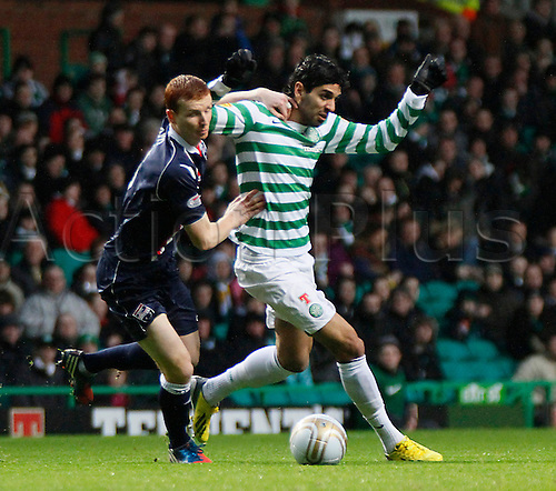 22.12.2012 Glasgow, Scotland. Lassad and Scott Boyd challenge for the ball during the Scottish Premier League game between Celtic and Ross County from Celtic Park.