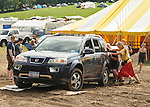 Falcon Ridge Volunteers and staff pushing a car that  is stuck in the mud near the Ticket Tent at the 24th Annual Falcon Ridge Folk Festival,held at Dodds Farm, Hillsdale NY on Sunday July 29, 2012. Photograph taken by Jim Peppler. Copyright Jim Peppler/2012