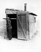 Doctor Robert H. Goddard observes the launch site from his launch control shack while standing by the firing control panel. From here he can fire, release, or stop testing if firing was unsatisfactory. The sandbags on the roof provide protection against possible accident. .Credit: NASA via CNP