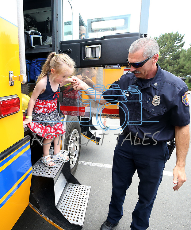 Jim White, with Carson City Fire, helps Isabella Cantwell, 3, climb out of a fire engine during the Touch-a-Truck event at the Carson City Library in Carson City, Nev., on Saturday, Aug. 5, 2017. <br /> Photo by Cathleen Allison/Nevada Photo Source