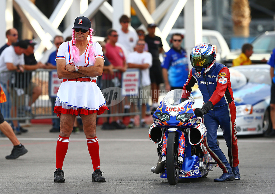 Oct 31, 2014; Las Vegas, NV, USA; NHRA pro stock motorcycle rider Hector Arana Sr (right) with a crew member wearing a Halloween costume during qualifying for the Toyota Nationals at The Strip at Las Vegas Motor Speedway. Mandatory Credit: Mark J. Rebilas-USA TODAY Sports