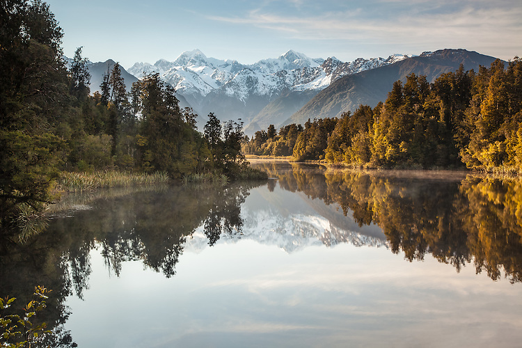 Perfect reflections of Mt Cook, Mt Tasman & Southern Alps at Lake Matheson, Westland Tai Poutini National Park NZ.