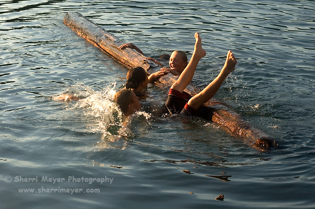 Teens log rolling at Sugar Pine Reservoir, near Foresthill California