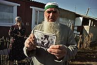 Majskij / Confine Ossezia-Inguscezia. <br /> Profughi ingusci fuggiti dall'Ossezia del Nord a causa degli scontri armati e delle tensioni etniche. Nella foto il vecchio jusuf mostra con orgoglio la fotografia dei suoi avi, l'unica cosa che gli resta del suo passato.<br /> Ingush refugees who fled South Ossetia as a result of armed conflicts and ethnic tensions. In the picture the old Jusuf proudly displays the photograph of his ancestors, the only thing that remains of its past.<br /> Photo Livio Senigalliesi