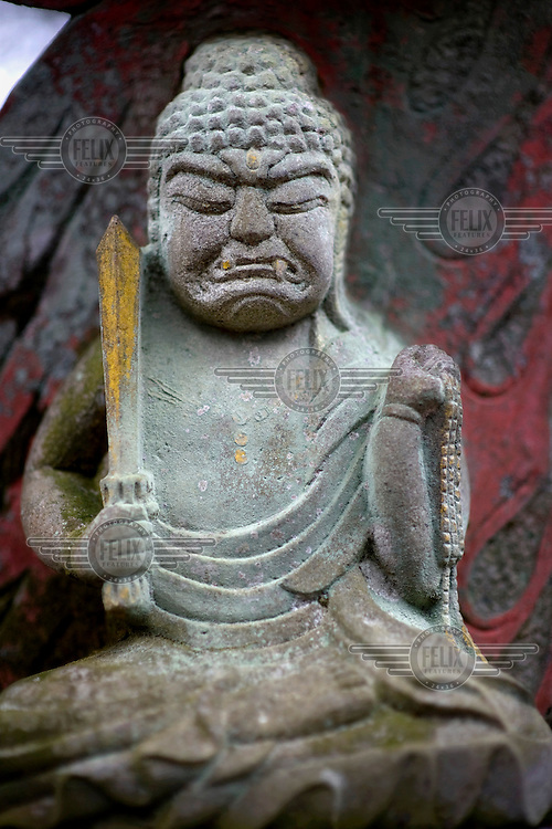 A carved stone Buddha figure on a building that is part of the Manmoyoji Temple in the Unzen Amakusa National Park. /Felix Features