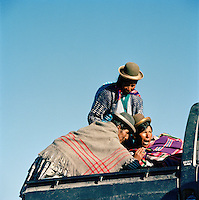 Three ladies in traditional dress on the back of a 4x4, Tomarapi, Sajama National Park, Oruro, Bolivia