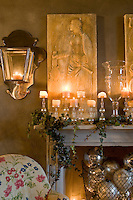 A mantelpiece in the living room is decorated with a collection of glass candlesticks