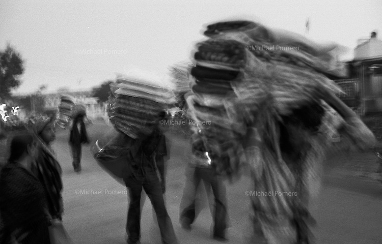 11.2010 Pushkar (Rajasthan)<br /> <br /> Men carrying bed covers during the fair.<br /> <br /> Hommes en train de porter des couvertures pendant la foire.