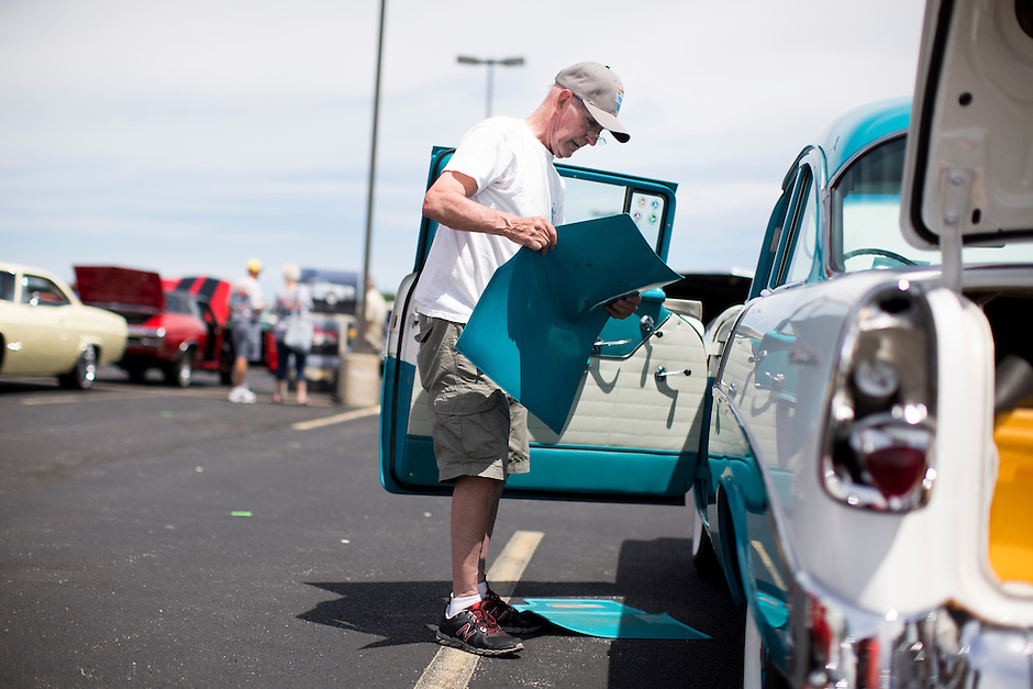 Dale Mealey puts floor mats in his 1956 Chevrolet 210 2-Door after show and shine judging during the 4th State Representative Chevy Show on Saturday, July 2, 2016, in Fort Wayne, Indiana. (Photo by James Brosher)