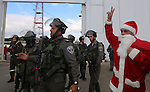A Palestinian protester dressed in a Father Christmas costume flashes a victory sign in front of members of the Israeli security forces during a demonstration against the Israeli settlements and demanding for free movement for the Palestinians during the Christmas period near a checkpoint in the West Bank biblical city of Bethlehem on December 23, 2014. Photo by Muhesen Amren